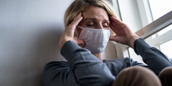 Woman with face mask indoors at home feeling stressed, mental health and coronavirus concept.