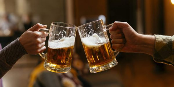 Close-up of two people toasting with beer.