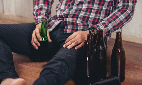 Alcohol addicted handsome man sitting alone with alcohol bottle